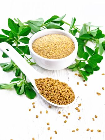 Fenugreek seeds in a spoon and ground spice in a bowl with leaves on wooden board background Zdjęcie Seryjne