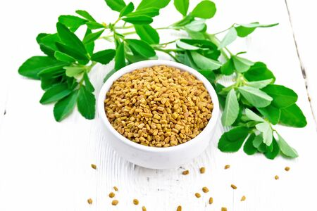 Nasiona kozieradki w misce i na stole, przyprawa liście na tle drewnianej deski