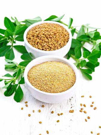 Fenugreek seeds and ground spice in two bowls and on a table with leaves on wooden board background Zdjęcie Seryjne