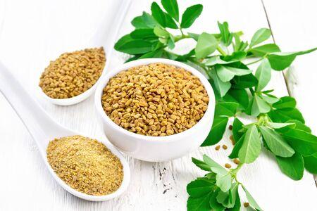 Nasiona kozieradki w misce i łyżce, mielona przyprawa w łyżce z zielonymi liśćmi na tle jasnej drewnianej deski Zdjęcie Seryjne