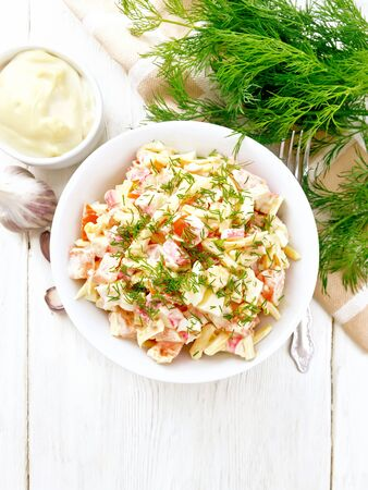 Salad of crab sticks, cheese, garlic, eggs and tomatoes, dressed with mayonnaise in a plate, kitchen towel and parsley on a wooden board background from above
