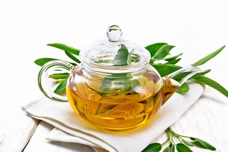 Herbal tea with sage in a glass teapot on a napkin on wooden board background