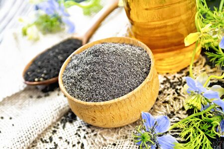 Flour of black caraway in a bowl, seeds in a spoon burlap, oil in bottle and twigs Nigella sativa with blue flowers and green leaves on wooden board background