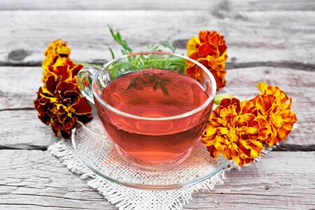Marigold herbal tea in a glass cup and saucer on a napkin of sackcloth, fresh flowers on background of an old wooden board