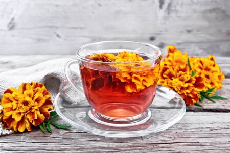 Marigold herbal tea in a glass cup and saucer, fresh flowers, sackcloth napkin on the background of an old wooden board