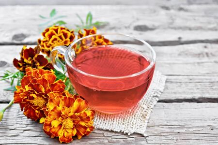 Marigold herbal tea in a glass cup, fresh flowers on a napkin of burlap on background of an old wooden board