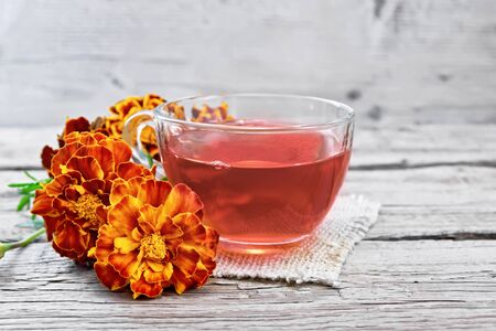 Marigold herbal tea in a glass cup, fresh flowers on a sackcloth napkin on a wooden board background