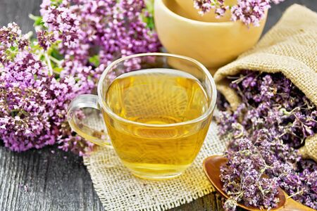Oregano herbal tea in a glass cup on burlap napkin, dried marjoram flowers in a bag and spoon, fresh flowers in mortar and on table on wooden board background