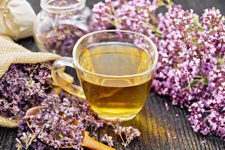 Oregano herbal tea in a glass cup, fresh flowers, dried marjoram flowers in a bag, jar and spoon on dark wooden board background