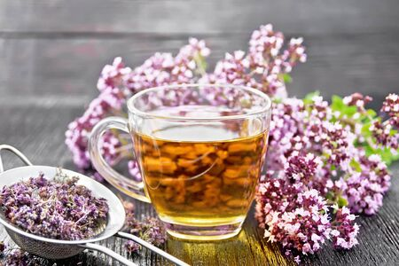 Oregano herbal tea in a glass cup, fresh flowers and metal strainer with dried marjoram flowers on dark wooden board