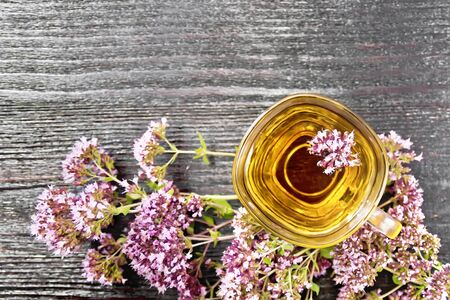 Oregano herbal tea in a glass cup, fresh pink marjoram flowers on wooden board background from above