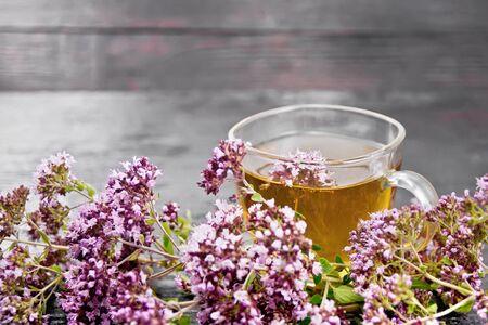 Oregano herbal tea in a glass cup, fresh pink marjoram flowers on dark wooden board background