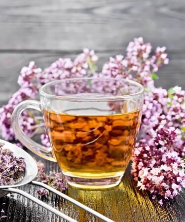 Oregano herbal tea in a glass cup, fresh flowers and metal strainer with dried marjoram flowers on wooden board