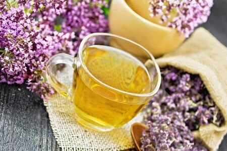 Oregano herbal tea in a glass cup on burlap napkin, fresh flowers in mortar and on the table, dry marjoram flowers in a bag and spoon on dark wooden board background
