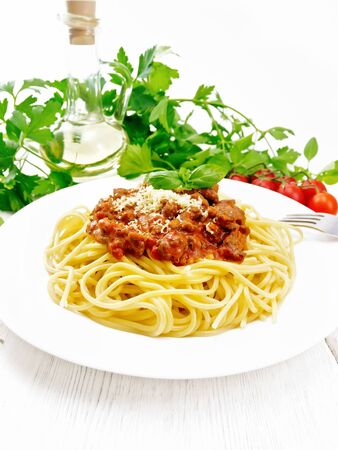 Spaghetti pasta with Bolognese sauce of minced meat, tomato juice, garlic, wine and spices with cheese and fork in a plate, vegetable oil, spicy herb on a white wooden board background