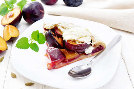 Piece of sweet pie with plum, sugar, cardamom and ice cream in a plate, sprigs of green mint, towel on wooden board background