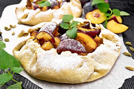 Two sweet pies with plums, sugar and cardamom on paper, sprigs of green mint on a dark wooden board background