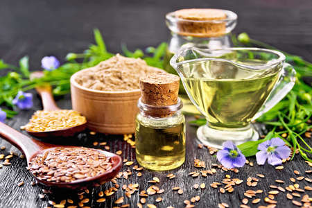 Linseed oil in two glass jars and a sauce boat with white and brown flax seeds in spoons, flour in a bowl, leaves and flowers on dark wooden board background