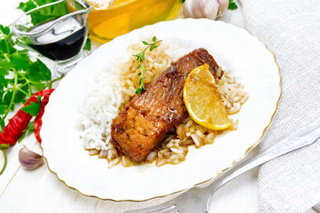 Pink salmon with honey, lemon juice and soy sauce, boiled rice, slice of lemon and sprig of thyme in a plate, hot pepper, garlic, parsley, towel and a fork on wooden board background