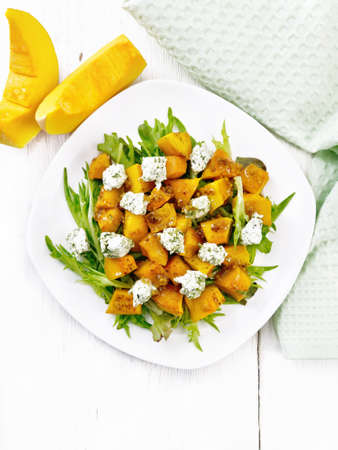 Salad of baked pumpkin, arugula with balls of salt cheese, seasoned with honey, grainy mustard, garlic and vegetable oil in a plate, napkin and fork on background of light wooden board from above