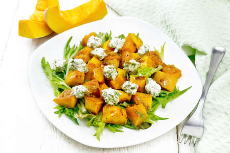 Salad of baked pumpkin, arugula with balls of salt cheese, seasoned with honey, mustard, garlic and vegetable oil in a plate, towel and fork on wooden board background Archivio Fotografico