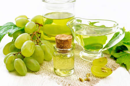 Grape oil in a bottle, gravy boat and a jar on a burlap napkin, berries and seeds of green grapes on white wooden board background