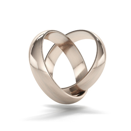 couple of gold wedding rings in heart shape isolated on a white background