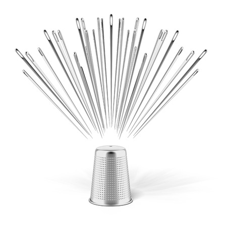 silver thimble and needles isolated on a white background photo