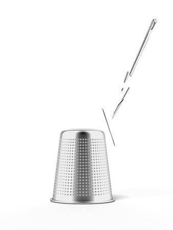 thimble and broken needle isolated on a white background photo