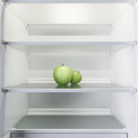 Two apples in open empty refrigerator isolated on a white background. 3d render photo