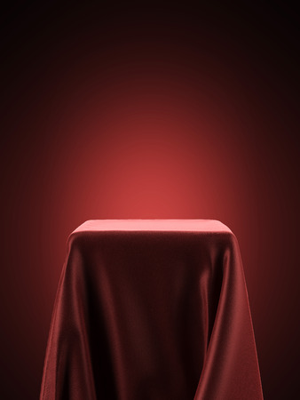 silk: pedestal covered with red cloth isolated on a red background. 3d render Stock Photo