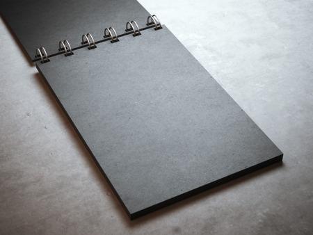 espiral: Cuaderno de espiral negro en el piso de concreto Foto de archivo
