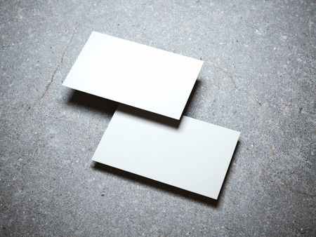 stack of business cards: Two blank white business cards on the concrete floor