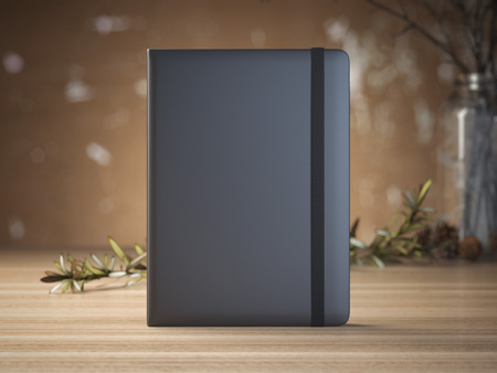 Black notebook on the light wooden table