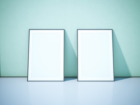 Two blank black picture frames on the green wall