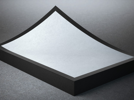 stack of papers: Stack of folded papers with black edges on the concrete floor