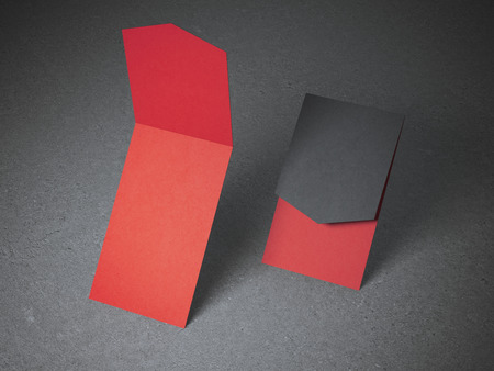 Two opened red business cards on concrete floor