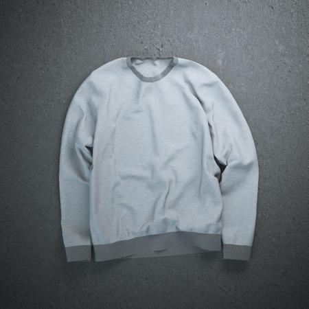 sweatshirt: Sudadera gris en el suelo de cemento oscuro Foto de archivo