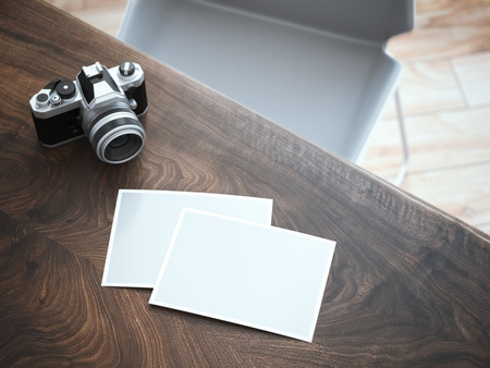 camera: stylish camera and blank photos on wooden table. 3d rendering