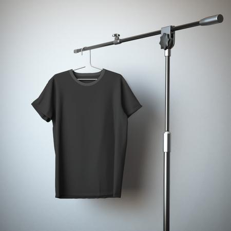 삼각대 스탠드에 검은 색 티셔츠 매달려