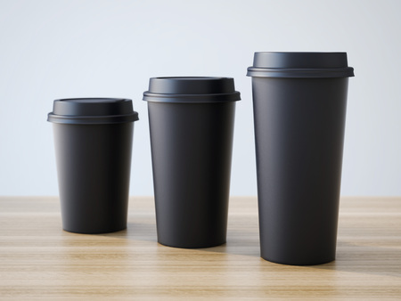 cappuccino cup: Three black cups on the wooden table.