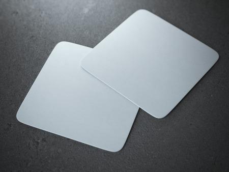 Twee witte vierkante bierviltjes in donkere studio Stockfoto