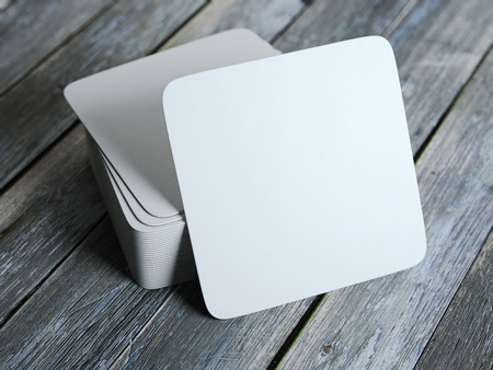 Stack of white square beer coasters on wooden floor