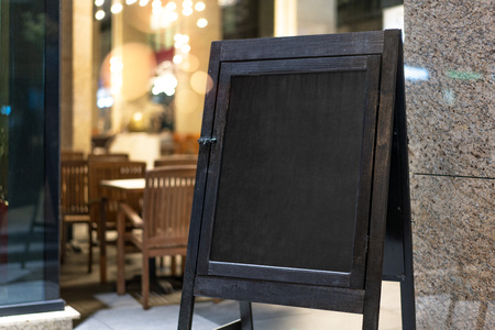 Close up of black sandwich board next to restaurant. Stock Photo
