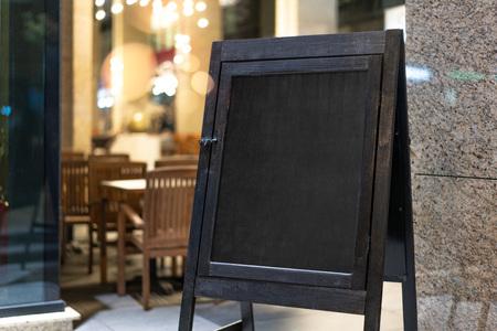 Close up of black sandwich board next to restaurant. Standard-Bild