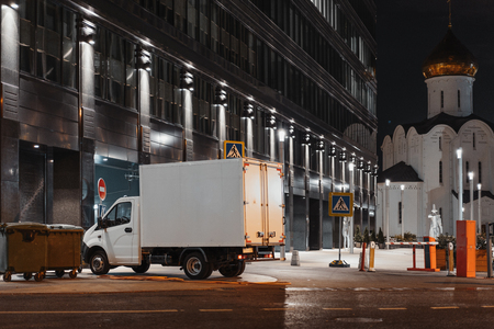 White truck at night city next to modern buildings.