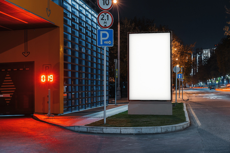 Blank white outdoor banner stand at night time in the city, 3d rendering. Фото со стока