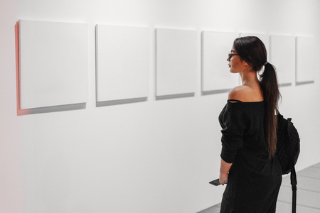 Close up of woman looking at blank canvas posters on the wall in art gallery.