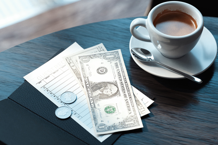 Close up of cheque, cash money and coffee cup in modern cafe. 3d rendering.