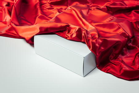Close up of white blank box under red cloth on white background. 3d rendering. Stok Fotoğraf